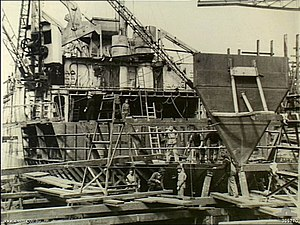 The stern of a ship undergoing repairs out of the water. The interior of the ship is exposed and cranes and workmen are working on the ship.