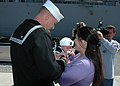 US Navy 050213-N-0874H-005 Fire Controlman 1st Class Chrisopher Johns embraces his new son with wife for the first time after returning from deployment aboard the guided missile destroyer USS The Sullivans (DDG 68).jpg