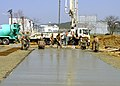 US Navy 050331-N-3113G-025 Seabees assigned to Naval Mobile Construction Battalion Four Zero (NMCB-40), Detachment Sasebo, and Japanese contractors pour and smooth-out concrete.jpg