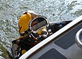 US Navy 050911-N-5345W-045 A U.S. Navy diver, assigned to Mobile Diving and Salvage Unit Two (MDSU-2), Detachment Two, swims alongside a U.S. Coast Guard patrol boat after repairing the vessel's damaged rudder and propell.jpg