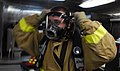 US Navy 090422-N-9928E-200 Damage Controlman Fireman Apprentice Michael Center, from Tucson, Ariz., dons a self-contained breathing apparatus on the mess decks during a simulated fire drill aboard the Arleigh Burke-class guided.jpg