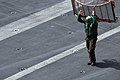 US Navy 090714-N-9132C-193 An aviation machinist's mate, assigned to the eagles of Strike Fighter Squadron 115 (VFA-115), carries a turn screen across the flight deck of the aircraft carrier USS Ronald Reagan (CVN 76).jpg