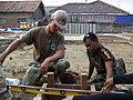 US Navy 090806-N-1831G-016 A Seabee assigned to Naval Mobile Construction Battalion (NMCB) 40 and an Indonesian marine engineer check the placement of a concrete form.jpg