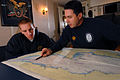 US Navy 091028-N-1688B-134 nsign Francis Dore, the navigator aboard the guided-missile destroyer USS Cole (DDG 67), reviews navigational charts with commanding officer Cmdr. Edward Devinney.jpg