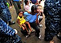 US Navy 100125-N-4774B-187 A Haitian woman and child are next in line to receive medical care from Sailors assigned to the guided-missile cruiser USS Bunker Hill (CG 52).jpg