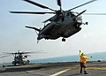US Navy 110210-N-8607R-210 Aviation Boatswain's Mate (Handling) 3rd Class Mario Teasley directs a CH-53E Sea Stallion helicopter to take off from t.jpg
