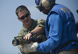 US Navy 120103-N-PB383-541 Lt. Anthony Petrosino explains to a Sailor how to properly man a fire hose during a flight deck firefighting exercise ab.jpg