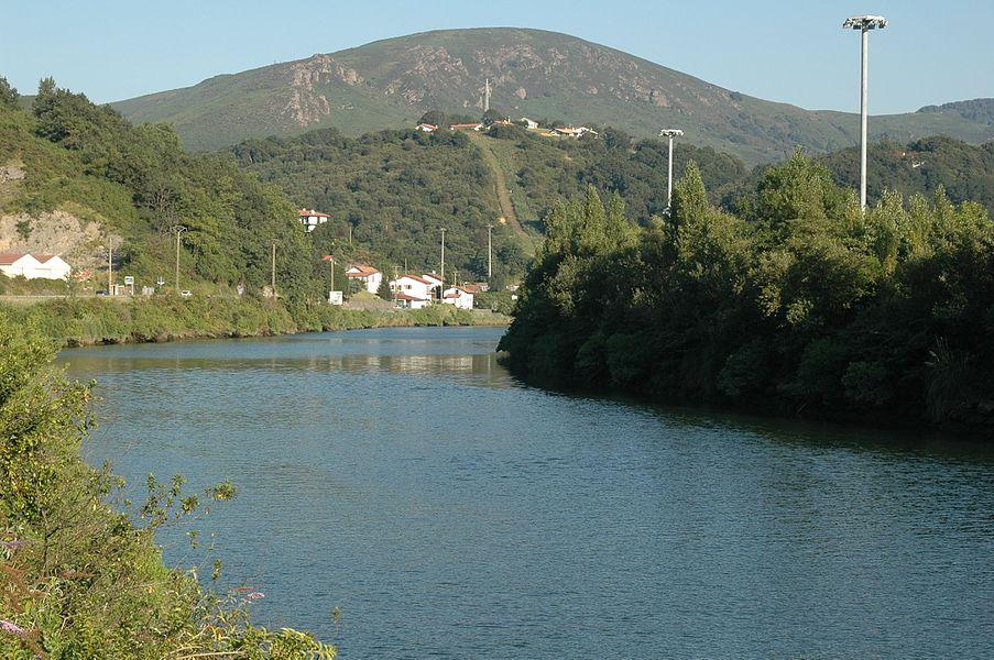 La Bidassoa, vue vers l'amont depuis la D811 près de la redoute Louis XIV. La commune de Biriatou est à gauche (en rive droite) de la Bidassoa (le village lui-même est derrière nous); l'Espagne est à droite (en rive gauche). Le hameau d'Aruntz et son pylône sont sur la première hauteur à mi-plan; ce qui semble être un chemin menant tout droit vers ce sommet, est le passage de lignes à haute tension. La barre rocheuse du Lumaberde est légèrement sur sa gauche (derrière ce sommet), et plus loin derrière le mont du Calvaire (277 m alt.). Le pont de Bénobie, sur le territoire d'Urrugne, est à environ 580 m derrière nous. Le pont de l'autoroute A63 est devant nous, juste après le coude de la rivière.