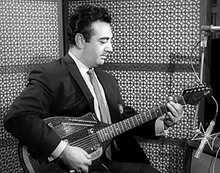 Black-and-white photo of guitarist wearing a suit while playing in the studio