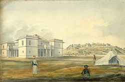 A white mansion and, in the distance, a fortified palace atop a hill. Three men stand near a tent in the foreground. The mansion has a large rust-colored shingled roof, pillared porches and open-air balconies on its four sides, and large box-like corner sections that extend out from the rest of the architecture.