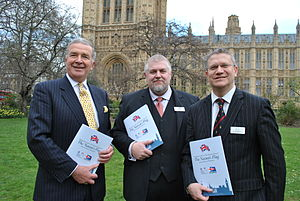 Flag Institute - Admiral Lord West, Charles Ashburner, and Andrew Rosindell MP celebrate the permanent flying of the Nation's flag over the Houses of Parliament