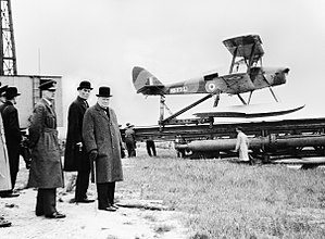 De Havilland Tiger Moth - Winston Churchill, David Margesson and others waiting to watch the launch of a DH.82 Queen Bee target drone, 6 June 1941.