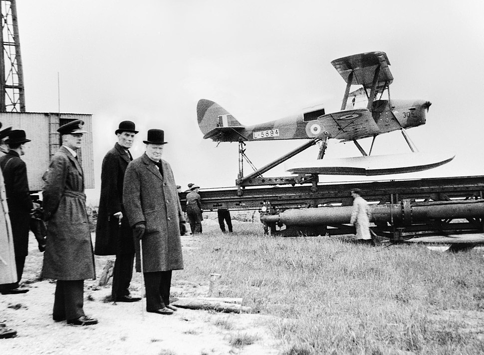 Winston Churchill and the Secretary of State for War waiting to see the launch of a de Havilland Queen Bee radio-controlled target drone, 6 June 1941. H10307