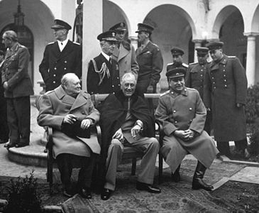 """Yalta Conference, February 1945. Original caption: """"Conference of the Big Three at Yalta makes final plans for the defeat of Germany. Here the """"Big Three"""" sit on the patio together, Prime Minister Winston S. Churchill, President Franklin D. Roosevelt, and Premier Josef Stalin. Behind them stand, from the left, Field Marshal Sir Alan Brooke, Fleet Admiral Ernest King, Fleet Admiral William D. Leahy, General of the Army George Marshall, Major General Laurence S. Kuter, General Aleksei Antonov, Vice Admiral Stepan Kucherov, and Admiral of the Fleet Nikolay Kuznetsov. February 1945. (Army) Exact Date Shot Unknown NARA FILE #: 111-SC-260486 WAR & CONFLICT BOOK #: 750"""""""