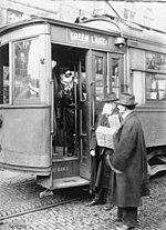 ein in der offenen Tür einer Straßenbahn stehender Schaffner verwehrt zwei Fahrgästen, von welchen einer ohne Maske die Straßenbahn betreten will, den Zutritt