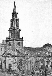 A black-and-white photograph of a church with a tall steeple, seen from its left across the street