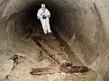 Photograph of a man in white overalls in a tunnel with an 1880s tunnel bore.