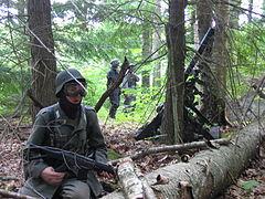 Pemain airsoft memainkan skenario Perang Dunia II dengan peralatan lengkap: seragam militer, senjata, kacamata pelindung, dan perlengkapan pelindung lainnya.
