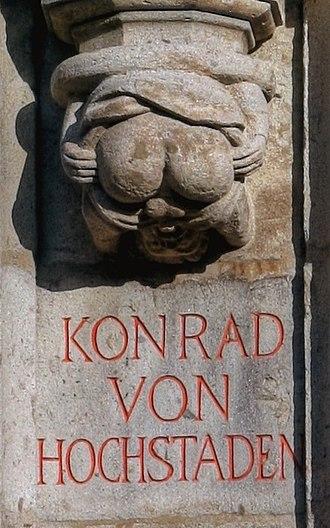 Autofellatio - An autofellatiating grotesque below a statue of Konrad von Hochstaden