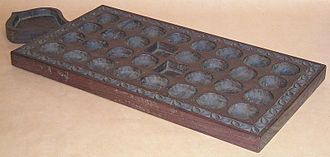 Bao (mancala game) - Traditional bao board from Zanzibar. As in most traditional boards, regular pits (mashimo) are round, while houses (nyumba) are square