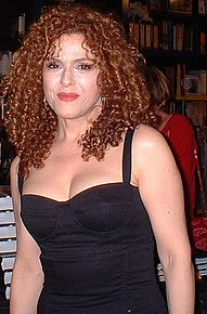 Middle-aged woman with long, curly hair wearing a black sleeveless dress.