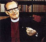 """Bo Giertz, a middle-aged man with dark-framed glasses, is seen in his office in front of a wall of books on shelves; he is wearing a plain white clerical collar, maroon shirt, large cross and black suit. His left arm is in the foreground; he is animated as if trying to make a point."""