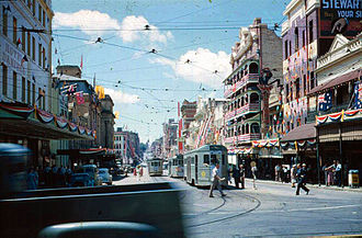 Trams in Brisbane - Trams and buildings in Adelaide Street decorated for the visit of Queen Elizabeth II in 1954