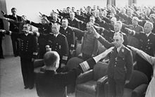 Photograph of dozens of Wehrmacht officers standing in a room and performing the Nazi salute