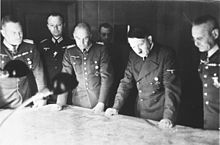 Photograph of Halder standing on Adolf Hitler's left side looking at a map with four other officers