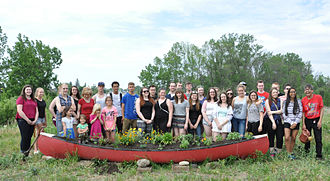 Waterdown, Ontario - Students from Waterdown District High School, and members of the community, plant the Souharissen Canoe Garden in 2015. The garden is filled with soil and medicine gifted by the Mississaugas of the New Credit Nation.