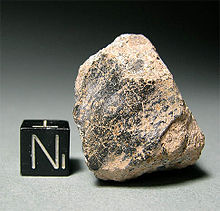 Lump of rock shown next to a much smaller cube to demonstrate relative size.