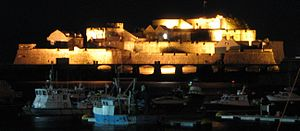 Guernsey - Castle Cornet seen at night over the harbour of St Peter Port.