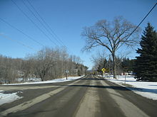Ground-level winter view of a two-lane rural road heading straight into the background. A second two-lane road begins at this road and leaves to the left foreground.