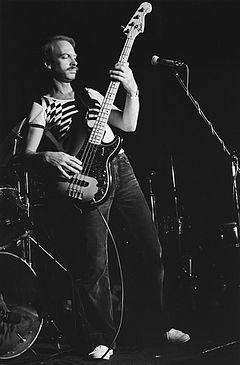 Brown is shown in a full length, black-and-white shot. He is leaning backwards and towards his right, with the bass guitar held at a steep angle. A microphone is in shot in front of him.