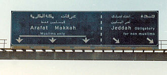 "Human rights in Saudi Arabia - Road sign on a highway into Mecca, stating that one direction is ""Muslims only"" while another direction is ""obligatory for non-Muslims"". Religious police are stationed beyond the turnoff on the main road to prevent non-Muslims from proceeding into Mecca and Medina."