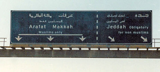 "Road sign on a highway into Mecca, stating that one direction is ""Muslims only"" while another direction is ""obligatory for non-Muslims"". Religious police are stationed beyond the turnoff on the main road to prevent non-Muslims from proceeding into Mecca and Medina.[46]"