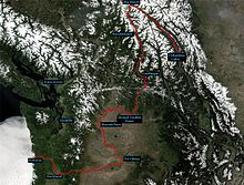 Modified satellite view of the Columbia River watershed showing the course of the river in red from Columbia Lake in British Columbia, Canada, to Astoria, Oregon, in the United States. The maps shows that the river, although flowing on average in a southwesterly direction from source to mouth, changes direction sharply from northwest to south at Big Bend in Canada, from south to west near Grand Coulee Dam in Washington, from west to south near Wenatchee, Washington, and from south to west near the Tri-Cities area in Washington.