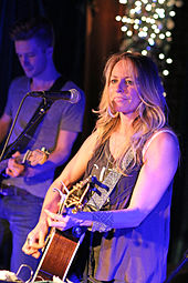 A woman with long blonde hair playing a guitar, with a man playing a guitar visible in the background