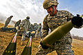 Defense.gov News Photo 101104-A-3843C-056 - U.S. Army Pvt. Darrell Futrell lifts a 155mm round weighing about 100 pounds at Camp Atterbury Joint Maneuver Training Center in central Indiana on.jpg
