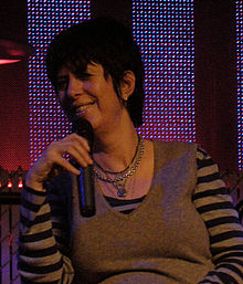 Diane Warren looking to the right and smiling while holding a microphone in her hand.