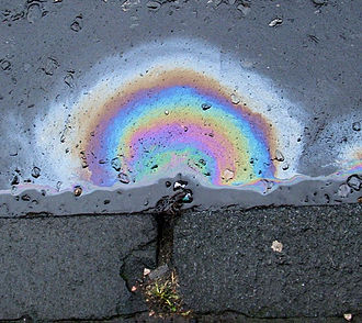 Iridescence - Fuel on top of water creates a thin film, which interferes with the light, producing different colours. The different bands represent different thicknesses in the film.