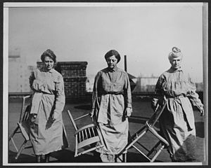 Doris Stevens - National Woman's Party members in prison dress carrying wooden chairs, on rooftop of building. (Left to right): Doris Stevens, Alison Turnbull Hopkins, and Eunice Dana Brannan, 1919