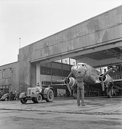 Twin-engined transport aircraft being towed from hangar by a tractor