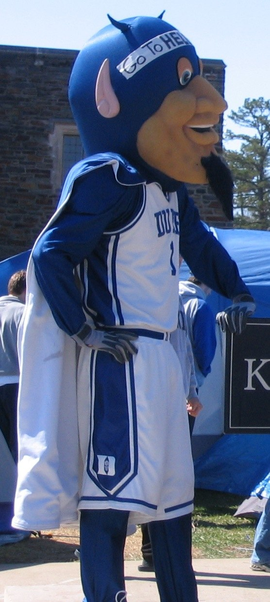 Duke Blue Devils mascot leans against sign with tents in background