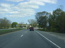 Ground-level of two lanes of a divided highway with a small grassy median; the highway intersects with another road at a traffic signal that is visible in the distance.