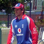 Um homem em uma camisa de críquete da Inglaterra de manga comprida e boné