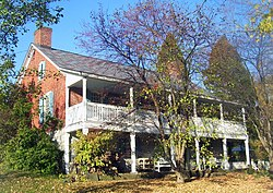 A brick house with full-width wooden porch and balcony seen from the left. A tree that has lost most of its leaves is in front, with other shrubs and trees at the side and rear.