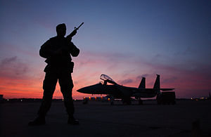 Otis Air National Guard Base - SSgt Nasam Rissvi guards an F-15 at Otis ANGB during a December sunset