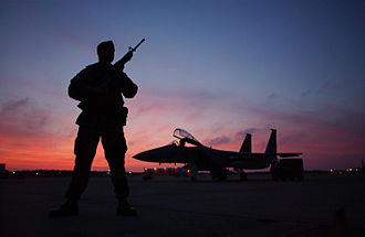 Otis Air National Guard Base - SSgt Nasam Rissvi guards an F-15 at Otis ANGB during a December sunset