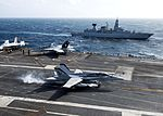 F-18C of VFA-83 lands on USS Eisenhower (CVN-69) with frigate Hamburg (F220) in the background 2013.jpg